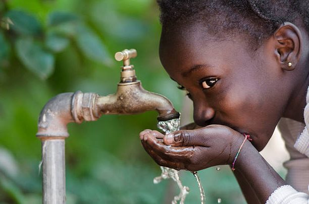 An African girl smiles as she drinks water froma tap